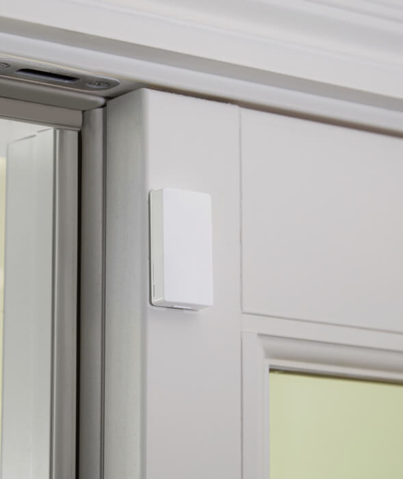 Mini Door/Window Sensor attached to a door with a white frame
