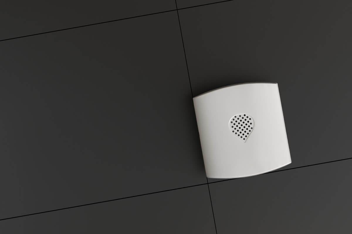 abode's water leak sensor on a black tiled background